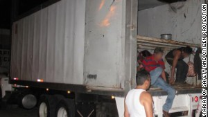 Migrants exit from the back of the truck.