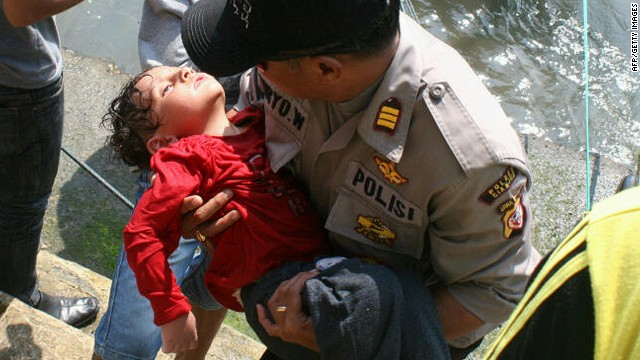 An Indonesian police man carries an exhausted asylum seeker boy rescued from waters off West Java on July 24, 2013.