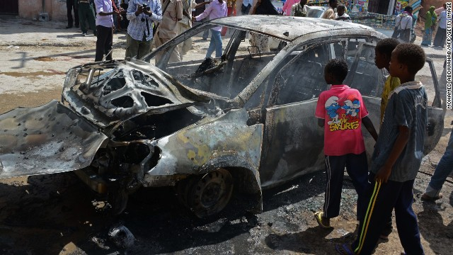 Somali children look at a burnt car after a bomb blast in Hamarweyne Market in Mogadishu on July 24, 2013.