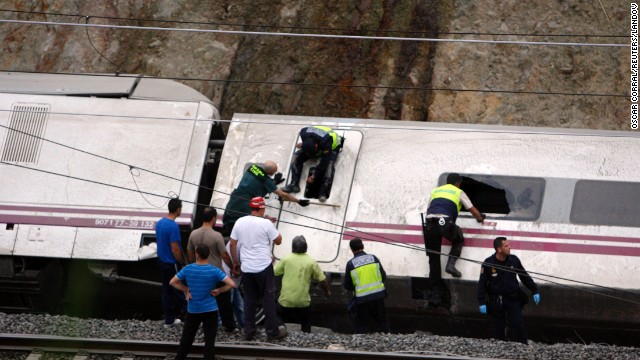 Rescuers work to pull victims from the derailed cars.