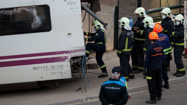 Emergency personnel work at the crash scene July 25. An investigation into the cause of the derailment is under way, but Spain's transportation minister says the train appears to have been going too fast.