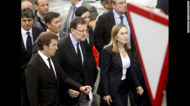 Spanish Prime Minister Mariano Rajoy, center, visits the crash site July 25 with Public Works Minister Ana Pastor, right, and Alberto Nunez Feijoo, head of the regional government in Galicia. The latter declared seven days of mourning for victims of the crash.<!-- --> </br>