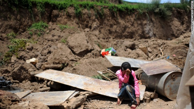 Song Xiaomei cries on Wednesday, July 24, after her home was destroyed by an earth