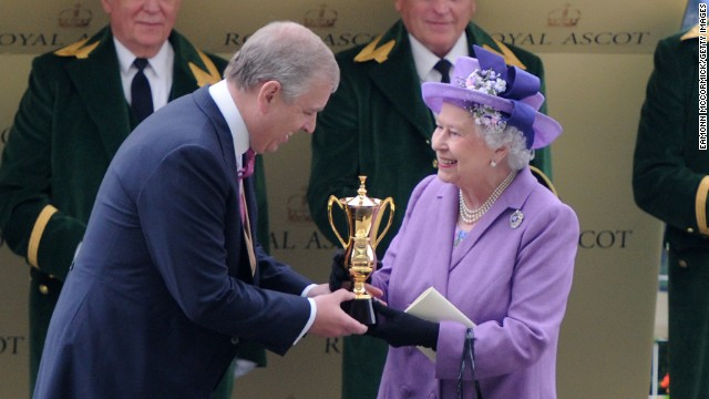 Queen Elizabeth II receives the Royal Ascot Gold Cup from her son Prince Andrew after her horse Estimate won the 2013 edition of the prestigious race.