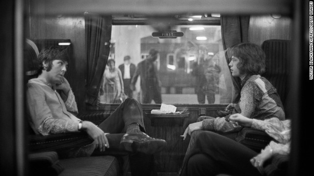 Paul McCartney of the Beatles, left, sits across from Jagger on a train at London's Euston Station in 1967.