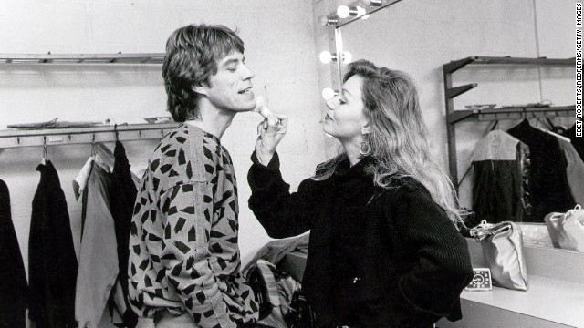 Makeup is applied to Mick Jagger's face backstage in 1984.