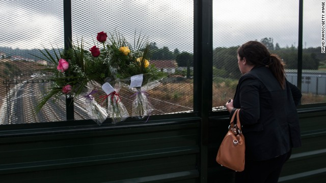 A woman looks on from a bridge where flowers were displayed in memory of the victims on July 26. The crash occurred on the eve of a public holiday, when more people than usual may have been traveling in the region.