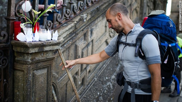 A man leaves his cane next to candles in memory of the train crash victims, on Friday, July 26, in Santiago de Compostela, Spain. A spokeswoman for the Galician regional government told CNN that at least 78 people were confirmed dead but that the number could rise to 80.