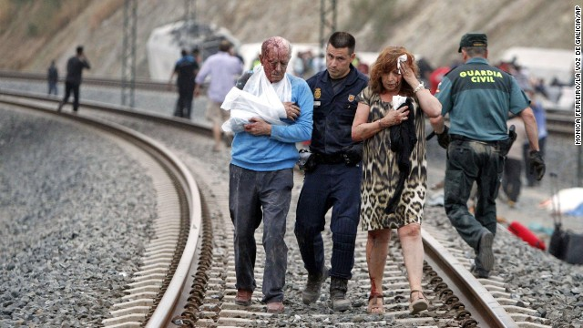 "Injured people are evacuated at the site of the July 24 train accident. The driver of the train is under detention and is being investigated for a ""crime,"" Spanish police said on July 26."