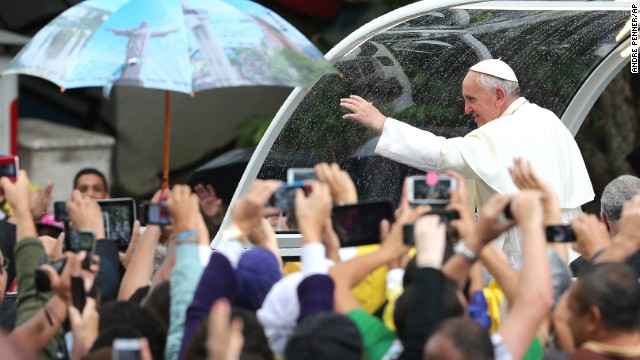 "Pope Francis waves to people from the ""Popemobile"" in Rio de Janeiro on July 27."