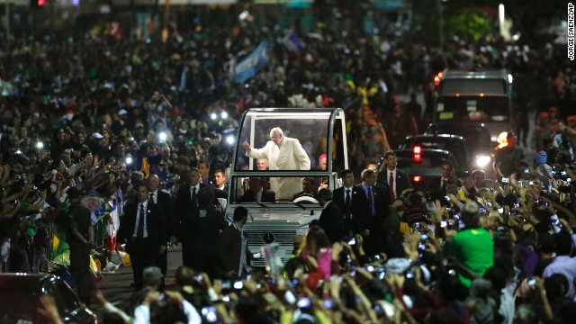 "Pope Francis waves from the ""Popemobile"" as it threads its way through the crowd waiting for the vigil to begin on July 27."