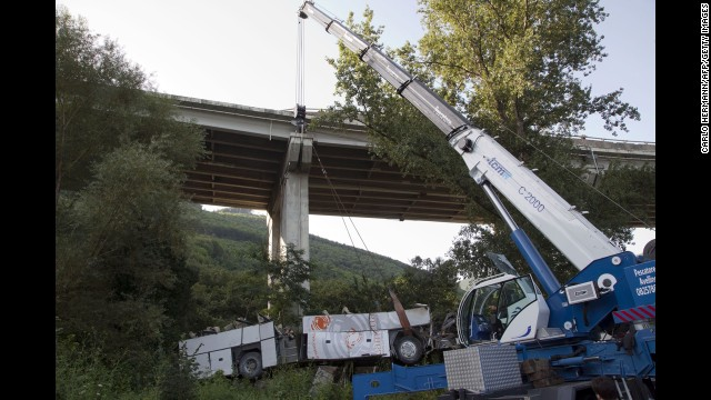 Workers remove the wreckage of a bus on Monday, July 29, near Baiano, Italy. The bus was returning pilgrims from a weekend visit to a Catholic shrine when it went off a bridge in southern Italy on Sunday, July 28, killing dozens of passengers, including some children, officials said.
