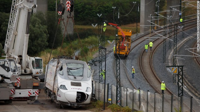 Wreckage of the front locomotive of a derailed train stands on the road while workers repair the railway on Sunday, July 28, in Santiago de Compostela, Spain. A spokeswoman for the Galician regional government said that at least 79 people were confirmed dead in the train crash. It occurred on the eve of a public holiday, when more people than usual may have been traveling in the region.