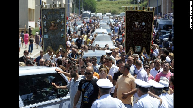 A crowd follows the hearses July 30.