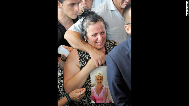 A distraught woman holds a picture of a crash victim at the funeral July 30.