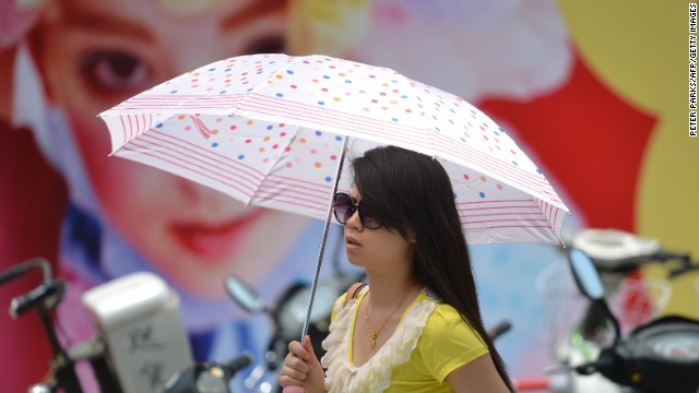 A woman uses an umbrella as sun protection as a heatwave hits Shanghai on Thursday, July 4.
