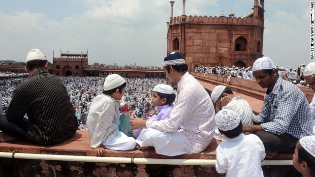 Observers sit on a ledge at the Jama Masjid overlooking a large crowd gathered for Friday prayers in New Delhi on August 2.