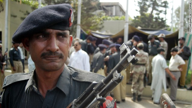 A Pakistani police officer stands guard outside the U.S. Consulate in Karachi after a gunman opened fire there on February 28, 2003. Two police officers were killed, and six others, including one civilian, were injured.