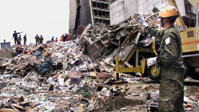 Rescue workers stand on the remains of a building in front of the U.S. Embassy in Nairobi, Kenya, on August 10, 1998, four days after a deadly attack. Twelve Americans were among more than 200 people killed in nearly simultaneous bombings at U.S. embassies in Nairobi and Dar es Salaam, Tanzania.