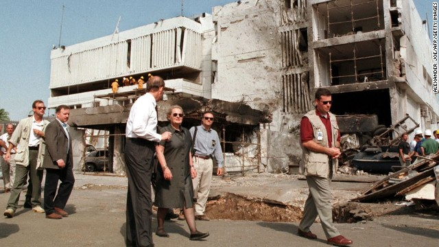 Secretary of State Madeleine Albright, center, walks past the damaged <a href='http://www.cnn.com/WORLD/africa/9808/08/africa.explosions.01/'>U.S. Embassy in Dar es Salaam</a> on August 18, 1998. The August 7 attacks in Tanzania and Kenya were later attributed to al Qaeda.