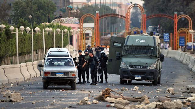 Egyptian riot police block the entrance to Sixth of October City in Giza on August 2 following clashes with Morsy supporters.