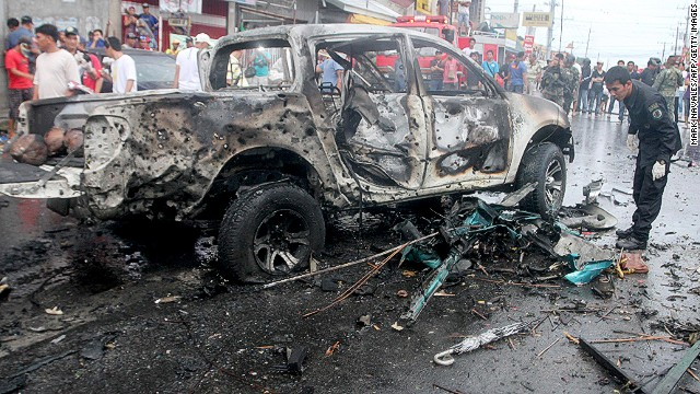 Investigators search among wreckage after a car bomb explosion in Cotabato city, Mindanao on August 5, 2013.