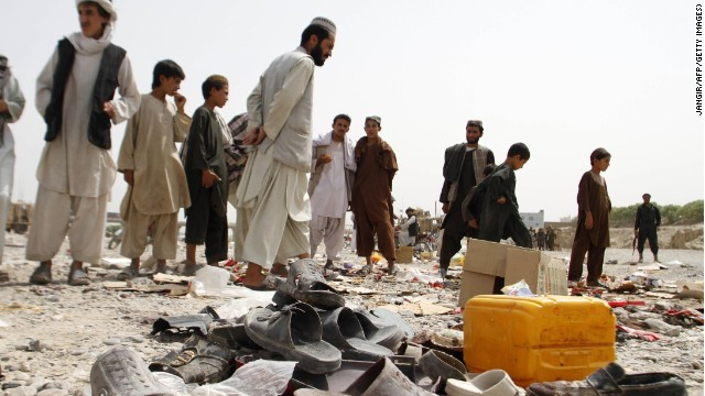 Men walk amidst debris from a bomb blast, strewn at the roadside on the outskirts of Kandahar on August 5, 2013.
