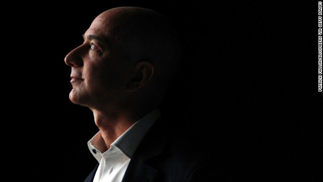 Jeff Bezos, chief executive officer of Amazon.com Inc., watches a video of the new Kindle Fire HD tablet at a news conference.