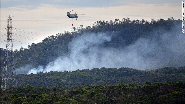 A U.S. military helicopter flies on a fire fighting operation after a U.S. military helicopter crashed on in Okinawa on August 5, 2013.