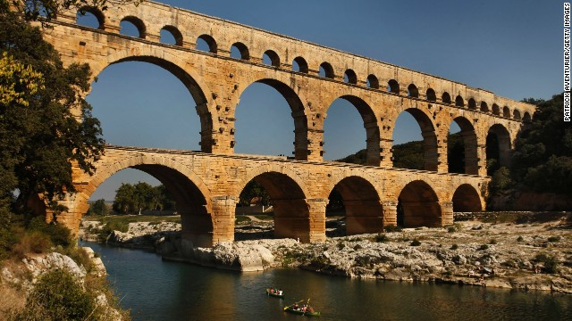 Le Pont Du Gard is an ancient Roman aqueduct bridge that crosses the Gard river in southern France. Built by the Romans in the 1st century AD, the bridge has three levels of arches and formerly carried an estimated 44 million gallons of water a day to the city of Nimes.