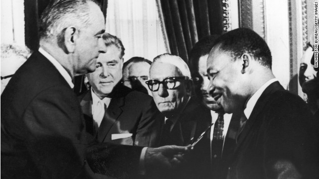 President Lyndon B. Johnson hands pen to civil rights leader Rev. Martin Luther King Jr. during the the signing of the Voting Rights Act in August,1965