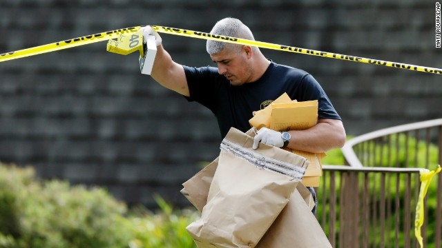 An investigator carries evidence away from the Ross Township Municipal Building crime scene on August 6.