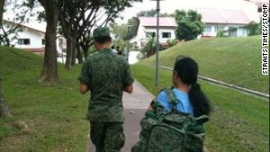 This picture of a maid carrying a SIngapore national serviceman\'s backpack went viral in 2011