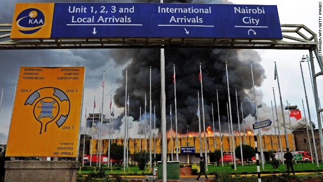 Authorities stand outside the burning airport on August 7.