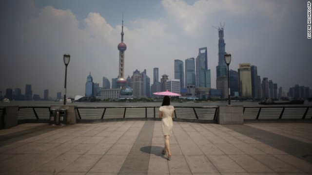 A woman uses a parasol to block the sun's rays at the Bund, a popular tourist spot in Shanghai, China, on August 7.
