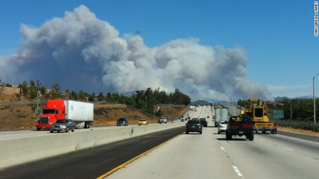 Smoke from the fast-moving fire billows across I-10 in Southern California.