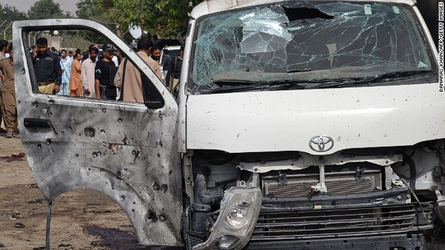 Pakistani police officials gather near the wreckage of a vehicle at the site of a suicide bomb attack in Quetta on August 8, 2013