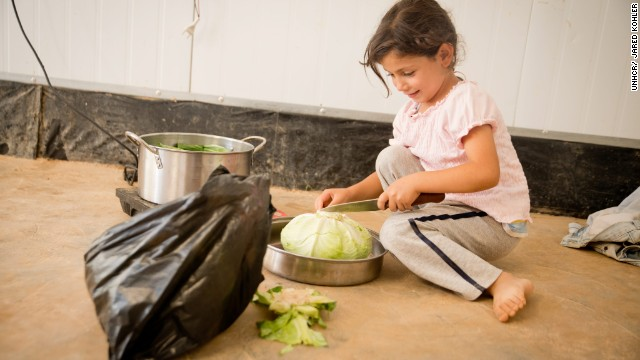 A young girl helps prepare the evening meal, <i>iftar</i>, with her family in Za'atari refugee camp.