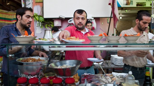 "Syrian chef, Galal (center), prepares the evening iftar meal during Ramadan at the busy Bab Elhara Restaurant in Cairo. He fled to Egypt a month ago with his wife and two children. <!-- --> </br>""I was away from Syria for eight years of my own free will, but now I'm away forcibly. As soon as things calm down, I will go back home,"" he said."