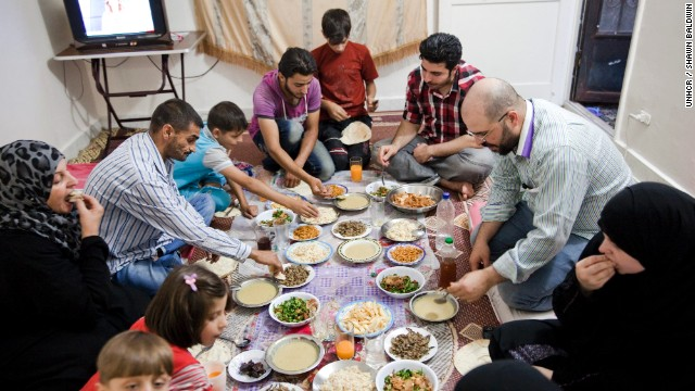"Ahmed, 48, (left) and his family share the Iftar meal during Ramadan in Cairo, Egypt. Ahmed spent four months in jail in Homs, Syria before fleeing with his wife and two children after their home was destroyed. ""I feel like I'm in heaven here because I spent the last 3 Ramadan's under gunfire,"" he said."