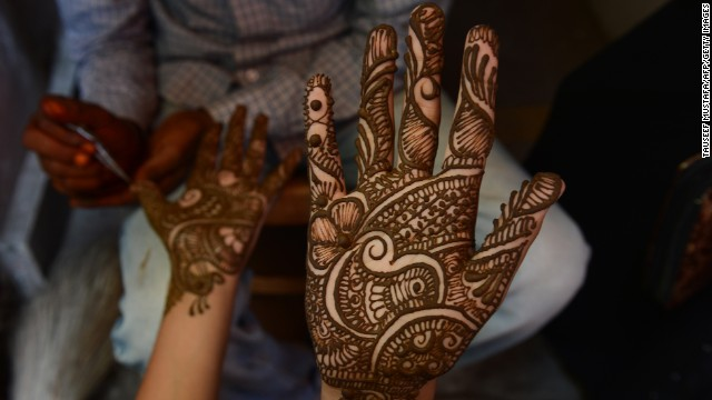 A young Kashmiri woman admires her hand after it was decorated with henna at a market ahead of the festivities on August 8. The word Ramadan derives from the Arabic ramida or ar-ramad, meaning a fierce, burning heat.