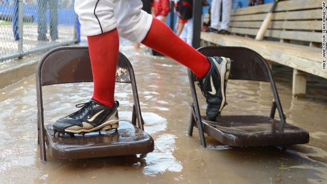 Players for minor league baseball team the Batavia Muckdogs try to escape a flooded dugout on a bridge of chairs during a rainstorm Thursday, August 8. The unplayable field conditions led to the cancellation of the game in Batavia, New York.
