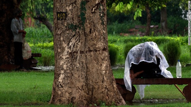A man takes cover under a plastic sheet during a rain shower in New Delhi on August 8.