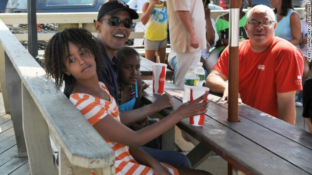 Obama waits for lunch with daughters, Malia, left, and Sasha, at a Martha's Vineyard restaurant in August 2009.