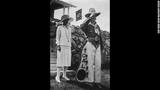President Calvin Coolidge poses in his personalized chaps with first lady Grace Coolidge at a party celebrating the Fourth of July and his 55th birthday at the Summer White House in South Dakota, 1927.