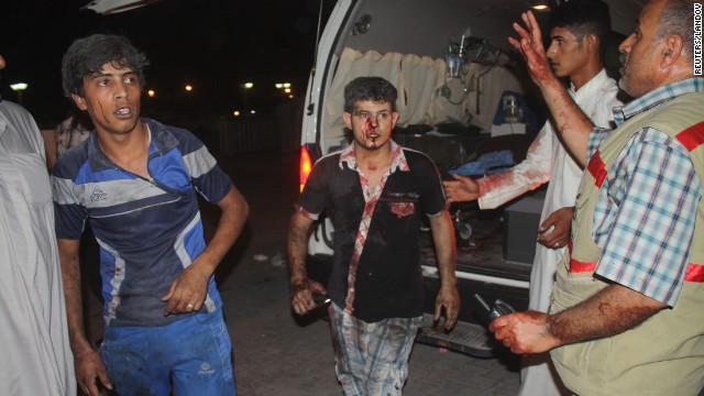 Victims of a car bomb attack in Nasiriyah City, south of Baghdad, emerge from the scene of an attack on Saturday, August 10.