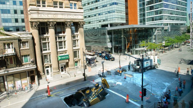 A backhoe is swallowed by a sinkhole in Montreal, Quebec, Canada, on August 6. The driver of the backhoe was not injured.