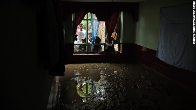 Afghan villagers check out damage inside their house in the Shakardara district of Kabul province on Sunday, August 11, after flash floods. More than 20 people have died in the area around the Afghan capital after heavy rainfall and flooding. Click through to see other images of weather around the world: