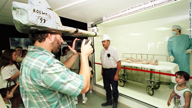A visitor wearing a home-made hat takes pictures of a scene displayed at the International UFO Museum and Research Center in downtown Roswell, New Mexico.