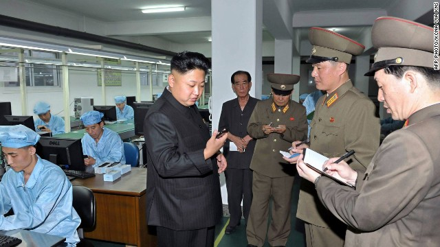 North Korean leader Kim Jong-Un inspects production of new touch-screen mobile phones.